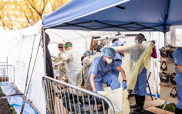 Medical workers putting on protective gear at the beginning of their shift at the emergency field hospital run by Samaritan's Purse and Mount Sinai Health System in Central Park on April 08, 2020 in New York, United States (Misha Friedman/Getty Images/AFP)