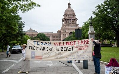 Protesters hold up a sign in front of the Texas State Capitol building on April 18, 2020 in Austin, Texas.  (Sergio Flores/Getty Images/AFP)