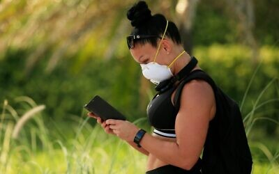 "A woman wearing a mask checks her phone on April 02, 2020 in Miami Beach, Florida. Florida Gov. Ron DeSantis signed a ""Stay-at-Home"" order Wednesday in response to the coronavirus (COVID-19) pandemic. (Cliff Hawkins/Getty Images/AFP)"