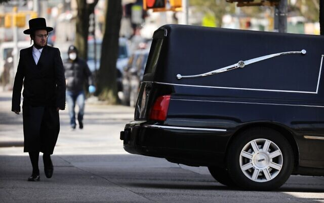 A man walks by a funeral home and hearse in the heavily Orthodox Borough Park neighborhood of Brooklyn on April 16, 2020 in New York City. (Spencer Platt/Getty Images/AFP)