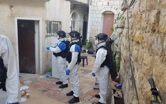 Israel Police wearing protective clothing seen in the Mea Shearim neighborhood of Jerusalem to arrest a man diagnosed with the coronavirus who broke quarantine orders April 6, 2020. (Israel Police)