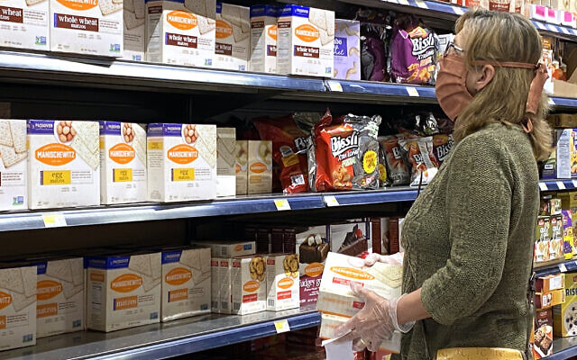A woman wears a mask while shopping for Passover items at a grocery store in Overland Park, Kan., April 7, 2020. (Jamie Squire/Getty Images via JTA)