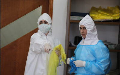 Palestinian health professionals standing in a quarantine facility in the northern West Bank city of Tulkarem on April 3, 2020. (Credit: Wafa)