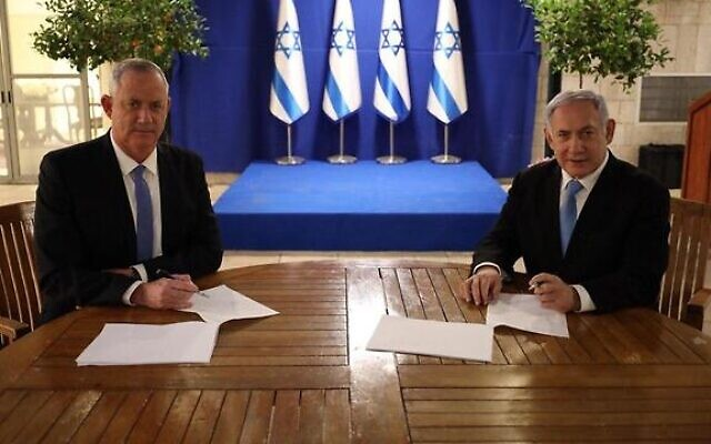 Blue and White leader Benny Gantz (left) and Prime Minister Benjamin Netanyahu sign their unity government agreement on April 20, 2020. (GPO)