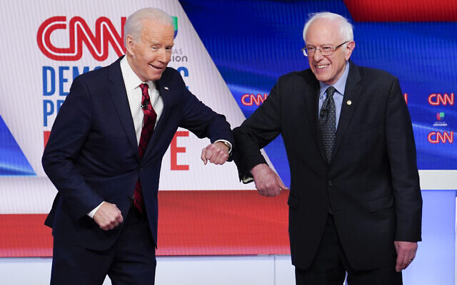 Former US vice president Joe Biden, left, and Vermont Senator Bernie Sanders, right, greet each other before they participate in a Democratic presidential primary debate at CNN Studios in Washington, March 15, 2020. (AP Photo/Evan Vucci)