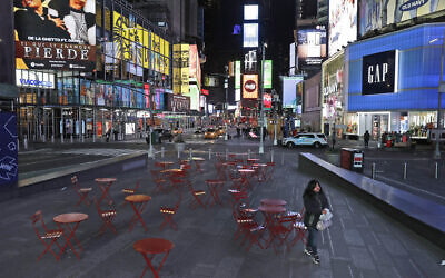 In this March 16, 2020 file photo, a woman walks through an almost empty Times Square in New York, March 16, 2020. (AP Photo/Seth Wenig)