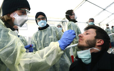 German medical employees demonstrate testing at a coronavirus test center for public service employees, during a media presentation in Munich, Germany, March 23, 2020. (AP Photo/Matthias Schrader, File)