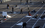 People prepare to sleep in areas marked by painted boxes on the ground of a parking lot at a makeshift camp for the homeless Monday, March 30, 2020, in Las Vegas. Officials opened part of the ot as a makeshift homeless shelter after a local shelter closed when a man staying there tested positive for the coronavirus. (AP Photo/John Locher)