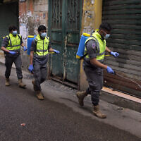 Islamic Health Society, an arm of the Iran-backed Hezbollah terror group spray disinfectant as a precaution against the coronavirus, in a southern suburb of Beirut, Lebanon, March 27, 2020. (Bilal Hussein/AP)