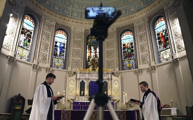 The Rev. Steven Paulikas, right, and curate Spencer Cantrell deliver an Evening Prayer service over Facebook Live in the Brooklyn borough of New York, March 29, 2020. (AP Photo/Emily Leshner)