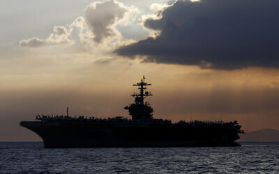 In this April 13, 2018, file photo the USS Theodore Roosevelt aircraft carrier is anchored off Manila Bay west of Manila, Philippines. The captain of the US Navy aircraft carrier facing a growing outbreak of the coronavirus is asking for permission to isolate the bulk of his roughly 5,000 crew members on shore, which would take the warship out of duty in an effort to save lives. The ship is docked in Guam (AP Photo/Bullit Marquez, File)