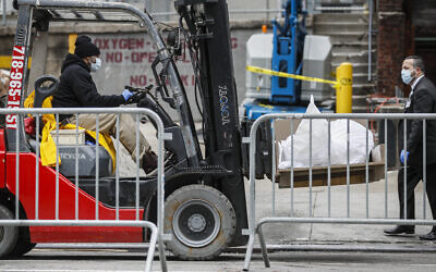 Bodies wrapped in plastic are loaded on to a refrigerated container truck operating as a makeshift morgue while being handled by medical workers wearing personal protective equipment due to COVID-19 concerns, Tuesday, March 31, 2020, at Brooklyn Hospital Center in the Brooklyn borough of New York. (AP Photo/John Minchillo)