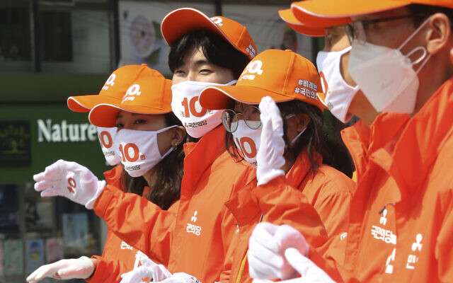 Supporters of the minor opposition People's Party wear face masks to help protect against the spread of the new coronavirus during a campaign for the 2020 South Korean National Assembly election in Seoul, South Korea, April 2, 2020. (AP Photo/Ahn Young-joon)