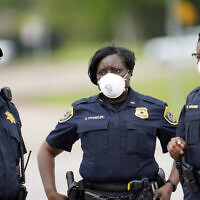 Law enforcement officers wear masks while working at a newly opened free drive through Covid-19 testing site provided by United Memorial Medical Center Thursday, April 2, 2020, in Houston. (AP Photo/David J. Phillip)