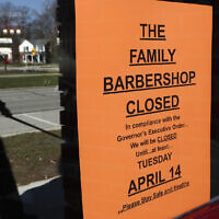 A pedestrian walks by The Family Barbershop, closed due to a Gov. Gretchen Whitmer executive order, in Grosse Pointe Woods, Michigan on April 2, 2020. (AP Photo/Paul Sancya)