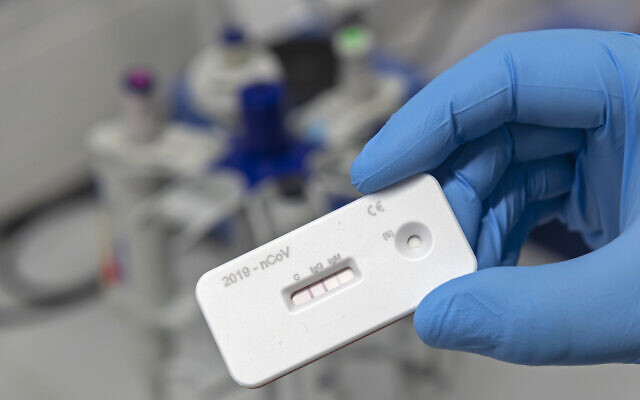 A scientist presents an antibody test for coronavirus in a laboratory of the Leibniz Institute of Photonic Technology (Leibniz IPHT) at the InfectoGnostics research campus in Jena, Germany, April 3, 2020. (AP/Jens Meyer)