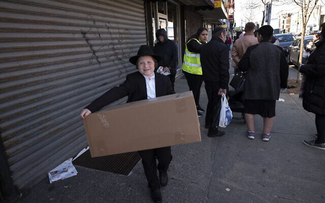 An boy carries a box of matzah for Passover that he picked up from his synagogue in the Brooklyn borough of New York, on March 26, 2020. (AP Photo/Mark Lennihan)