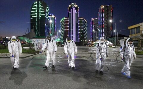Municipal workers wearing protective suits spray disinfectant in an area in the center of Grozny, Russia, Monday, April 6, 2020. Ramzan Kadyrov, strongman leader of Russia's province of Chechnya, has taken extreme measures to fight the spread of the new coronavirus in the region, vowing Monday not to let anyone who is not a formal resident of Chechnya into the area. (AP Photo/Musa Sadulayev)