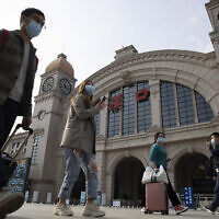 Travelers with their luggage walk past the Hankou railway station on the eve of its resuming outbound traffic in Wuhan in central China's Hubei province on April 7, 2020. (AP Photo/Ng Han Guan)