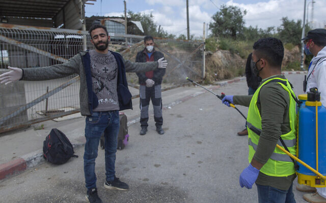 A paramedic from the Palestinian Authority Ministry of Health disinfects Palestinian laborers to help contain the coronavirus, as they exit an Israeli army checkpoint after returning from work in Israel, near the West Bank village of Nilin, west of Ramallah, April 7, 2020. (AP Photo/Nasser Nasser)
