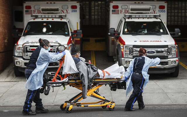 Patients are brought into Wyckoff Heights Medical Center by staff wearing personal protective gear due to COVID-19 concerns on April 7, 2020, in the Brooklyn borough of New York. (AP/John Minchillo)