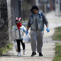 In this April 7, 2020 photo, Erica Harris, right, and her daughter Jordan, wear their protective masks as they walk back home after getting a lunch and homework from the child's school on Chicago's Southside in Chicago (AP Photo/Charles Rex Arbogast)