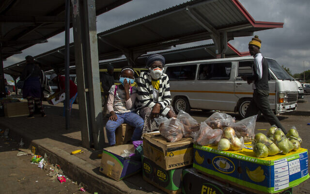 A woman and her daughter wearing face masks to protect against coronavirus sell fruit and vegetables at the taxi station in Lenasia, south of Johannesburg, South Africa, April 8, 2020. (AP Photo/Themba Hadebe)