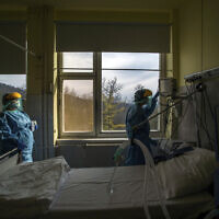 In this March 24, 2020, file photo, medical staff members check a ventilator in protective suits at the care unit for the new COVID-19 infected patients inside the Koranyi National Institute of Pulmonology in Budapest (Zoltan Balogh/MTI via AP, File)