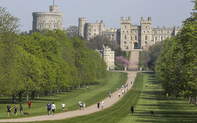 People exercise social distancing as they take their exorcise on the Long Walk in front of Windsor Castle during the Easter bank holiday weekend, as the UK continues in lockdown to help curb the spread of the coronavirus, in Windsor, England, April 10, 2020.  (Steve Parsons / PA via AP)