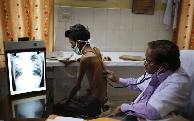 In this March 24, 2014, file photo, a doctor examines a tuberculosis patient in a government TB hospital in Allahabad, India. (AP Photo/Rajesh Kumar Singh, File)