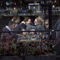 A couple hug and laugh as they have lunch in a restaurant in Stockholm, Sweden, April 4, 2020. (AP Photo/Andres Kudacki, File)