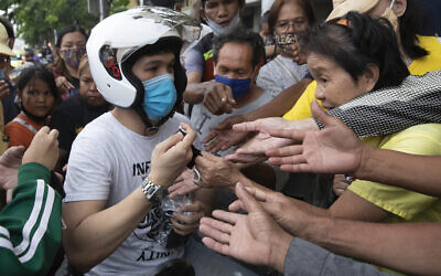 A motorist, white helmet, offers free face masks to locals to help curb the spread of the coronavirus in Bangkok, Thailand, on April 13, 2020. (AP Photo/Sakchai Lalit)
