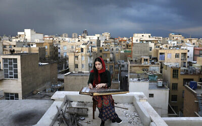 In this March 26, 2020, photo, Mojgan Hosseini, a 28-year-old member of the National Orchestra of Iran, plays Qanun on the roof of her home during mandatory self-isolation due to the new coronavirus disease outbreak, in Tehran, Iran. (AP Photo/Ebrahim Noroozi)