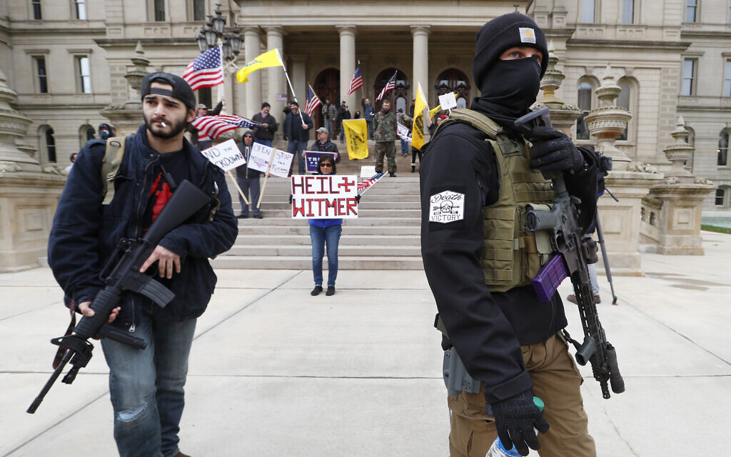 Protesters carry rifles near the steps of the Michigan State Capitol building in Lansing, Michigan, April 15, 2020. (AP Photo/Paul Sancya)