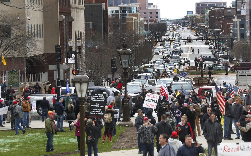 Protesters gather at the Michigan State Capitol in Lansing, Mich., Wednesday, April 15, 2020. Flag-waving, honking protesters drove past the Michigan Capitol on Wednesday to show their displeasure with Gov. Gretchen Whitmer's orders to keep people at home and businesses locked during the new coronavirus COVID-19 outbreak. (AP Photo/Paul Sancya)