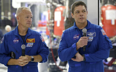 In this October 10, 2019, photo, NASA astronauts Bob Behnken, right, and Doug Hurley talk to the media in front of the Crew Dragon spacecraft at SpaceX headquarters in Hawthorne, California. (AP Photo/Alex Gallardo)
