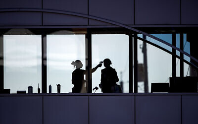 In this April 10, 2020, file photo, amid coronavirus concerns, a US healthcare worker takes the temperature of a visitor to Essentia Health who was crossing over a skywalk bridge from the adjoining parking deck, in Duluth, Minnesota. (Alex Kormann/Star Tribune via AP, File)