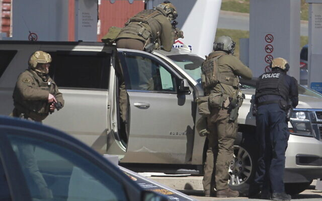 Royal Canadian Mounted Police officers confront the suspect of a shooting rampage at a gas station in Enfield, Nova Scotia on Sunday April 19, 2020.  (Tim Krochak/The Canadian Press via AP)