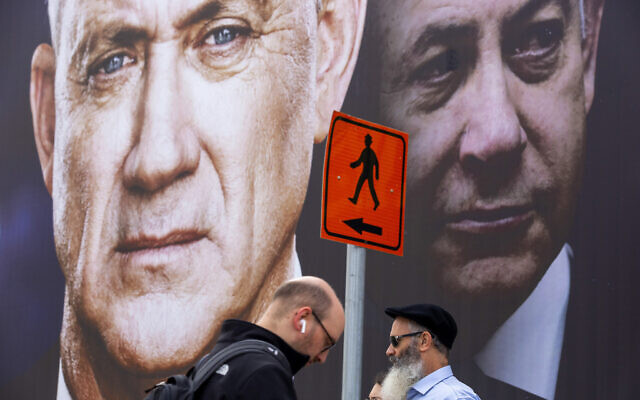 People walk past an election campaign billboard for the Blue and White party in Ramat Gan, February 23, 2020 (AP Photo/Oded Balilty, File)