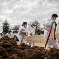 US gravediggers carry the casket of someone presumed to have died from coronavirus as they are buried without any family present at Mount Richmond Cemetery in the Staten Island borough of New York, April 7, 2020. (AP Photo/David Goldman)