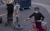 Children wear protective face masks in Tel Aviv, March 24, 2020. (AP Photo/Oded Balilty)