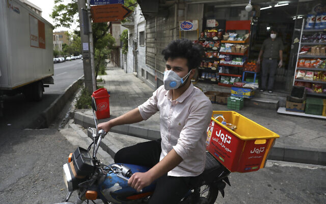 In this April 21, 2020 photo, grocery delivery man Saeed Vatanparast, wearing a protective face mask to help prevent the spread of the coronavirus, leaves on his motorcycle for a delivery, in Tehran, Iran. (AP Photo/Vahid Salemi)