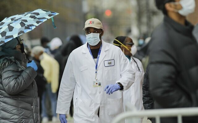 A US medical worker walks past people lined up at Gotham Health East New York, a COVID-19 testing center, on April 23, 2020, in the Brooklyn borough of New York. (AP Photo/Frank Franklin II)