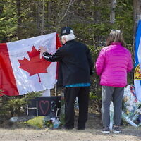 In this Wednesday, April 22, 2020, photo, a couple place a flag at a memorial in Portapique, Nova Scotia, following Saturday's shooting rampage. (Andrew Vaughan/The Canadian Press via AP)
