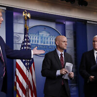 President Donald Trump gestures to Vice President Mike Pence as Stephen Hahn, commissioner of the US Food and Drug Administration, steps back to the podium to answer a question during a briefing about the coronavirus in the James Brady Press Briefing Room of the White House, Friday, April 24, 2020, in Washington. (AP Photo/Alex Brandon)