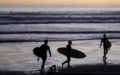 Surfers prepare to enter the water at Sumner Beach as COVID-19 restrictions are eased in Christchurch, New Zealand, April 28, 2020. (AP Photo/Mark Baker)