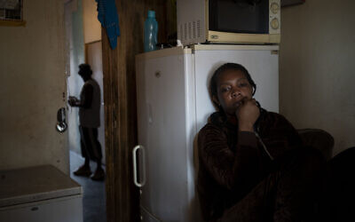 A woman sits inside her room in downtown Johannesburg, South Africa, on April 14, 2020. (AP Photo/Bram Janssen)