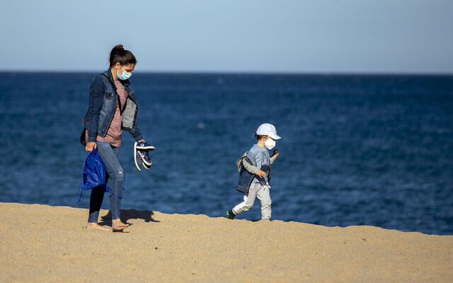 A woman and her son wear face masks as they walk on a beach in Badalona, near Barcelona, Spain, April 28, 2020 as the lockdown to combat the spread of coronavirus continues. (AP Photo/Emilio Morenatti)