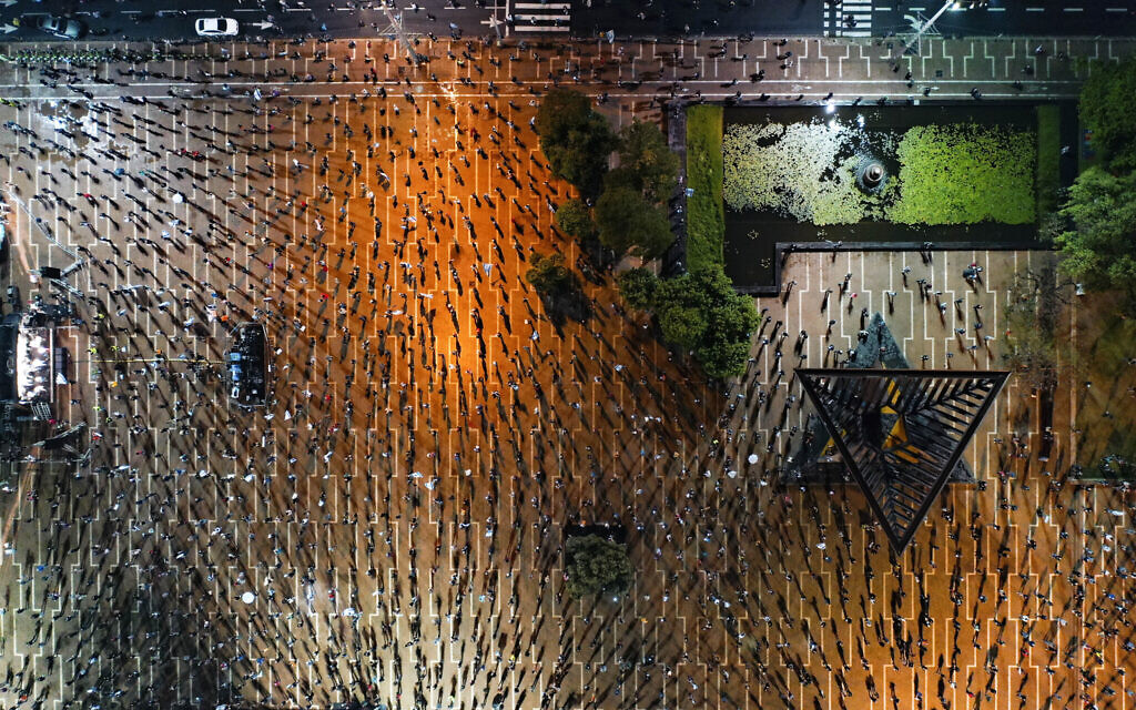 In this April 25, 2020 photo, people keep social distancing amid concerns over the country's coronavirus outbreak, during a 'Black Flag' protest against Prime Minister Benjamin Netanyahu and government corruption, at Rabin Square in Tel Aviv. (AP Photo/Oded Balilty)