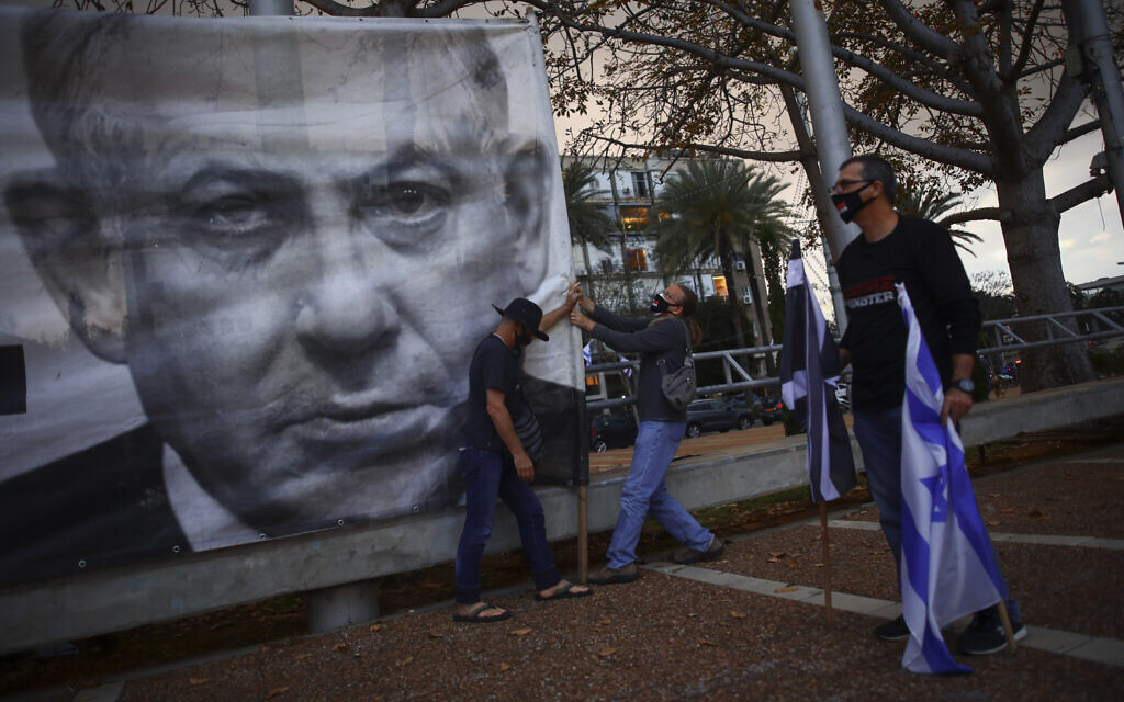 "In this Saturday, April 25, 2020 photo, demonstrators wearing protective face masks amid concerns over the country's coronavirus outbreak, hang a banner showing Israeli Prime Minister Benjamin Netanyahu during ""Black Flag"" protest against Netanyahu and government corruption, at Rabin Square in Tel Aviv, Israel.  (AP Photo/Oded Balilty)"
